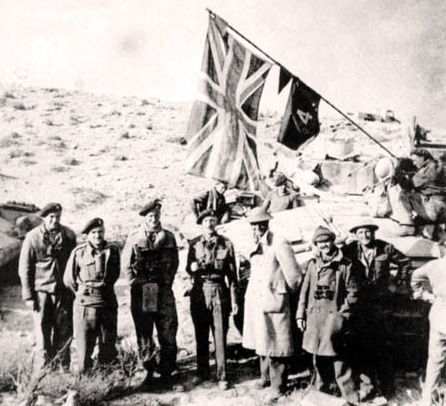 The link-up at Ed Duda. From left to right: three Tank Corps officers unnamed, Brigadier A.C. Willison, Lt-Col S.F. Hartnell, a Tank Corps officer unnamed, and Captain E.D. Blundell.This flag flew on the fortress in Tobruk until the town fell to Rommel's Afrika Korps on 21st June, 1942.
